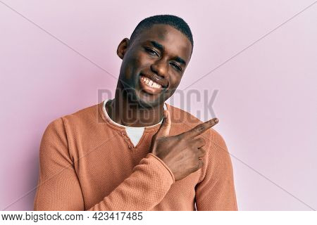 Young african american man wearing casual clothes cheerful with a smile of face pointing with hand and finger up to the side with happy and natural expression on face