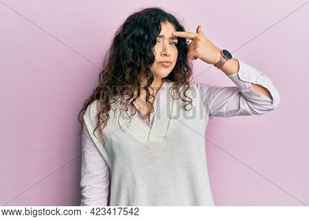 Young brunette woman with curly hair wearing casual clothes pointing unhappy to pimple on forehead, ugly infection of blackhead. acne and skin problem