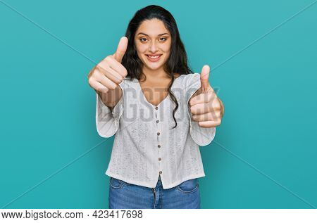 Brunette young woman wearing casual clothes approving doing positive gesture with hand, thumbs up smiling and happy for success. winner gesture.