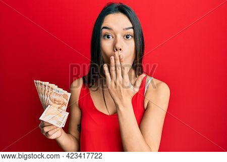 Young hispanic girl holding 50 turkish lira banknotes covering mouth with hand, shocked and afraid for mistake. surprised expression