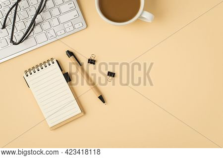Top View Photo Of White Keyboard Glasses Cup Notebook Pen And Binders On Isolated Beige Background W