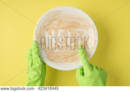 Top View Photo Of Hands In Green Rubber Gloves Indicating With Forefinger On Dirty Plate With Inscri
