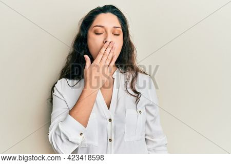 Beautiful middle eastern woman wearing casual clothes bored yawning tired covering mouth with hand. restless and sleepiness.