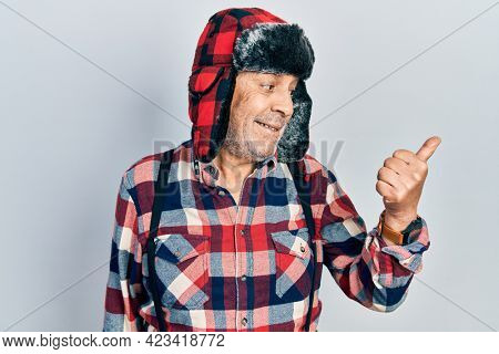 Handsome mature man wearing winter hat with ear flaps smiling with happy face looking and pointing to the side with thumb up.