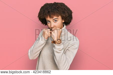 Young hispanic girl wearing wool winter sweater ready to fight with fist defense gesture, angry and upset face, afraid of problem