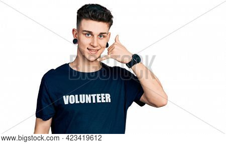 Young caucasian boy with ears dilation wearing volunteer t shirt smiling doing phone gesture with hand and fingers like talking on the telephone. communicating concepts.