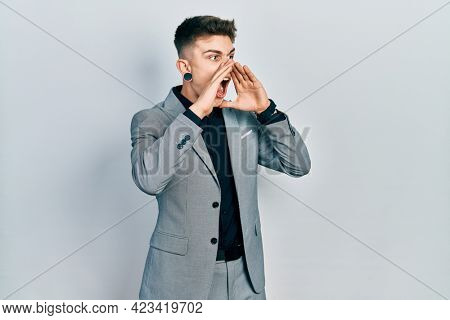 Young caucasian boy with ears dilation wearing business jacket shouting angry out loud with hands over mouth