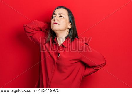 Middle age hispanic woman wearing casual clothes suffering of neck ache injury, touching neck with hand, muscular pain