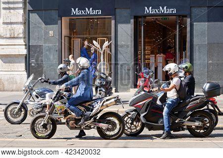 Milan, Italy - July 20, 2020. Motorbike Commuting. Man In Mask Riding Motorbike In Busy City Street