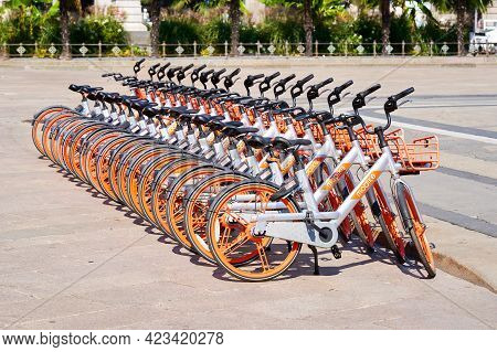 Bicycle Rental Service Mobike Stand In Row Parking On Duomo Square. Orange Bicycles With Basket For