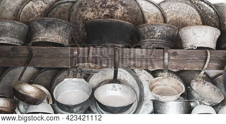 Collection Of Old Metal Pan Pot And Kitchenware Hanging On The Wall In A Traditional Cooking Kitchen