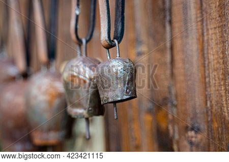 Perspective View Closeup Of Metal Rusted Cowbells With Leather Collar Isolated On Brown Wooden Backg