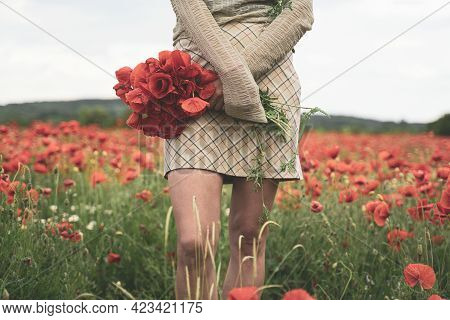 Front View Closeup Of Young Woman With Light Colored Clothing Holding A Bouquet And Picking Poppies