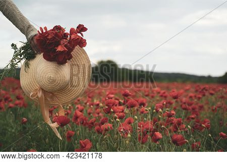 Front View Closeup Of Young Woman Hand Holding A Bouquet Of Poppies And A Wicker Hat With Scarf In A