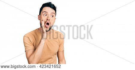 Hispanic man with beard wearing casual t shirt hand on mouth telling secret rumor, whispering malicious talk conversation