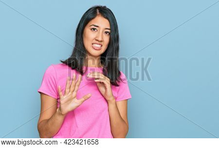 Beautiful asian young woman wearing casual pink t shirt disgusted expression, displeased and fearful doing disgust face because aversion reaction. with hands raised