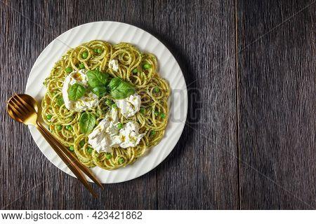 Spaghetti Salad With Pesto Sauce, Green Peas, Basil Leaves And Burrata Cheese On A Plate On A Dark R