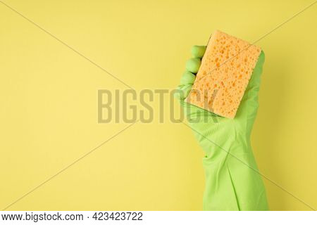 Above Photo Of Cellulose Sponge And Green Gloves Isolated On The Yellow Background