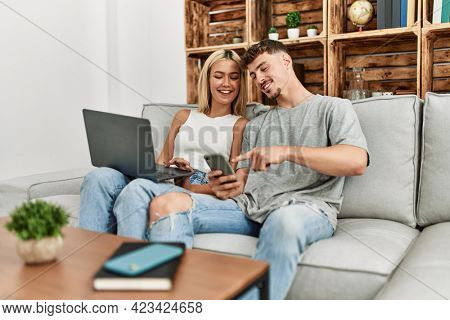 Young caucasian couple smiling happy using laptop and smartphone sitting on the sofa at home.