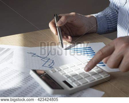 Male Hand At Desk With Financial Document With Graph Of Growing Trend, Making Calculations, Preparin