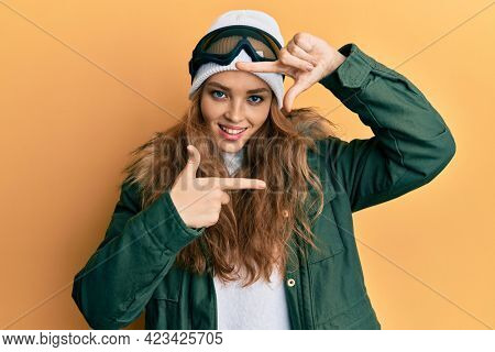 Beautiful blonde caucasian woman wearing snow wear and sky glasses smiling making frame with hands and fingers with happy face. creativity and photography concept.