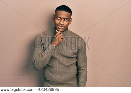 Young black man wearing casual turtleneck sweater with hand on chin thinking about question, pensive expression. smiling with thoughtful face. doubt concept.