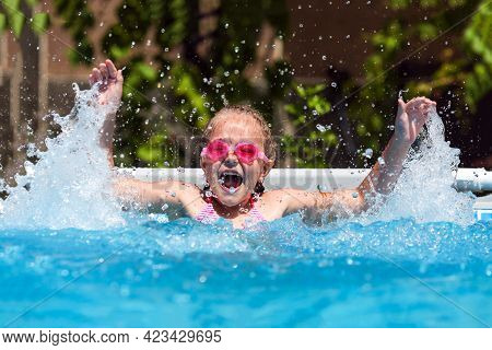 Cute Little Girl Smiling In Goggles In The Pool On A Sunny Day. The Child Splashing Water In The Poo