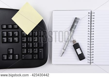 Business Desk: Overhead view of a  notebook with a yellow post-it note, accompanied by a black computer keyboard with pen and thumb drive.