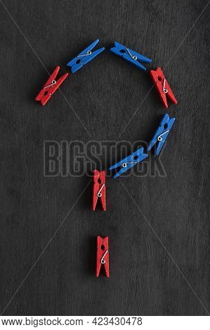 Clothespins In The Form Of Question Mark On Black Background. Question Mark Made From Colorful Cloth