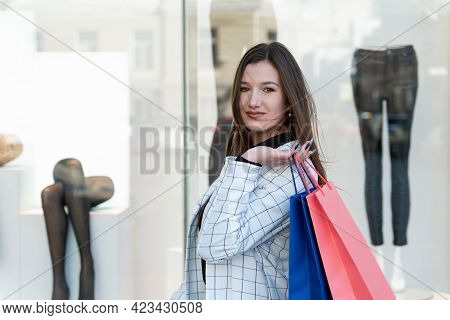 Portrait Of Brunette Woman With Colorful Packets In Hands On Showcase Background Of Clothing Store.