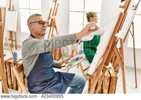Two middle age artist concentrated painting at art studio.