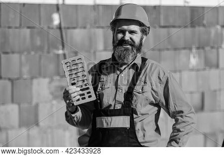 Element In Masonry Construction. Builder Hold Brick. Bearded Man Wear Hard Hat At Construction Site.