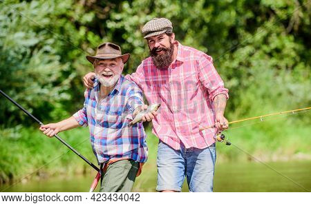 Grandpa And Mature Man Friends. Fishing With Spinning Reel. Sunny Summer Day At River. Fisherman Fam