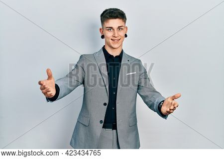 Young caucasian boy with ears dilation wearing business jacket looking at the camera smiling with open arms for hug. cheerful expression embracing happiness.