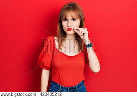 Redhead young woman wearing casual red t shirt mouth and lips shut as zip with fingers. secret and silent, taboo talking