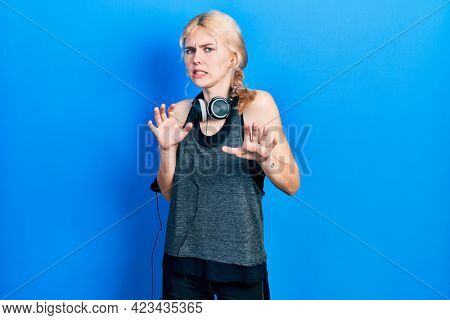 Beautiful caucasian woman with blond hair wearing sportswear disgusted expression, displeased and fearful doing disgust face because aversion reaction. with hands raised