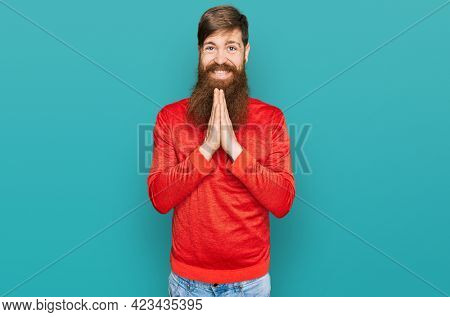 Redhead man with long beard wearing casual clothes praying with hands together asking for forgiveness smiling confident.