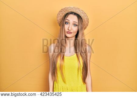 Young blonde girl wearing summer hat looking sleepy and tired, exhausted for fatigue and hangover, lazy eyes in the morning.