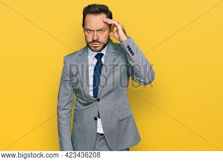 Middle age man wearing business clothes worried and stressed about a problem with hand on forehead, nervous and anxious for crisis