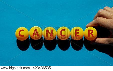 Medical And Cancer Symbol. The Concept Word 'cancer' On Orange Table Tennis Balls On A Beautiful Blu
