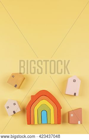 Rainbow Flag Colors Toy House And Small Pastel Color Wooden Houses On Yellow Background