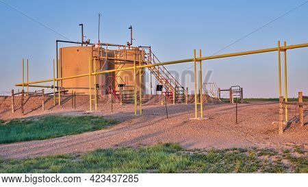 oil extraction facility with a crude oil tanks in a green prairie, Pawnee National Grassland in Colorado