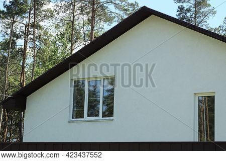 Large White Concrete Attic Of A Private House With Windows Behind A Brown Fence Outside