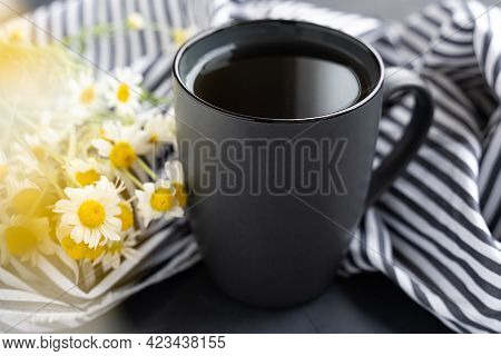 Chamomile Tea And Chamomiles In Gray Ceramic Cup On The Black Cement Table. Herbal Tea. Top View. Fl