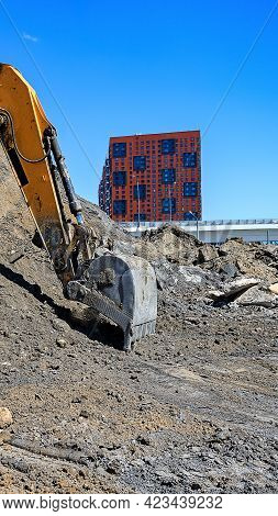 Bucket Of An Earthmover Digging A Pile Of Sand On The Background Of New Houses Under Construction At