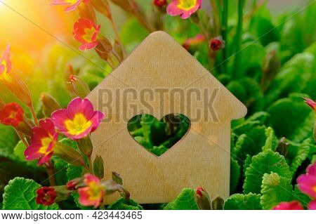 Mock-up Of A Wooden House On A Background Of Purple Flowers, Greenery And Sunlight. Heart Shaped Win
