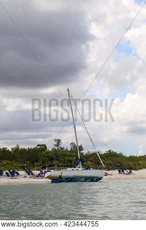 Shipwrecked Sailboat On The Beach Of Clam Pass In Naples, Florida Seen From A Kayak.