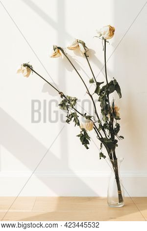 Dried white roses in a clear vase on a wooden floor