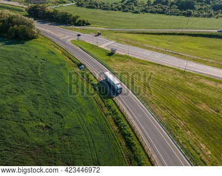 Aerial Top View of White Truck with Cargo Semi Trailer Moving on Road in Direction. Highway intersection junction