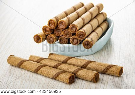 Brown Striped Wafer Rolls In Light-blue Bowl, Three Wafer Rolls On Wooden Table